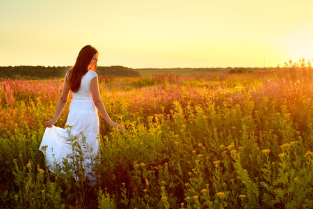 Young woman in white clothes standing in field on sunset photo