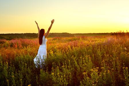 manos levantadas al cielo: Mujer joven en la ropa blanca de pie en el campo en la puesta del sol Foto de archivo