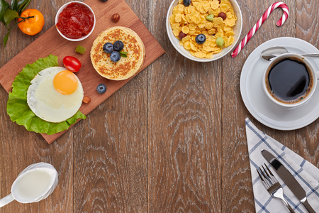 top view of pancake with blueberries and fried eggs with tomatoes and lettuce on a desk and a cornflakes in a bowl, and a cup of coffee with empty space