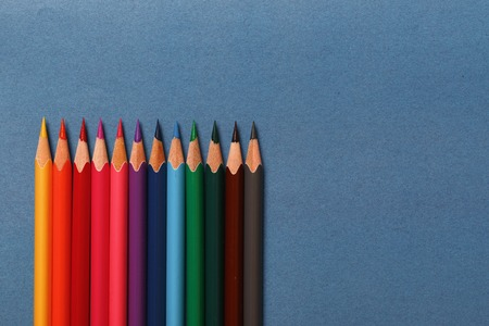 Multicolored pencils lie on a blue background Stock Photo
