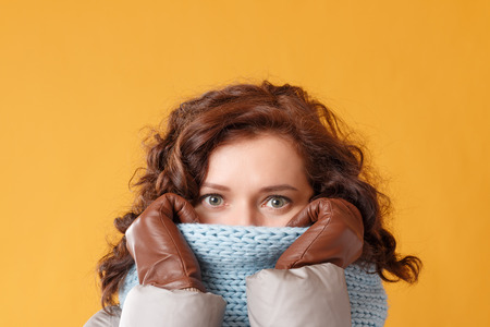 Portrait of a young woman on a yellow background. The beautiful brunette wears knitted snood, leather gloves. The concept of winter. Standard-Bild