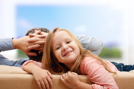 Happy family, dad and daughter preschooler together spend time. A man is a rear view, relaxsingon the couch and looking out the window, a little girl looks straight into the camera
