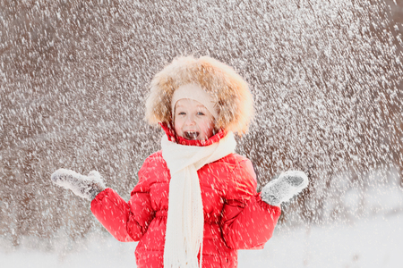 A happy little girl in a red suit is standing under falling snow in the forest. A child plays on a winter walk in the fresh air.