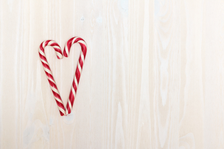Valentines Day. The composition of the heart of the Christmas candy on a light wooden background with texture. Top view