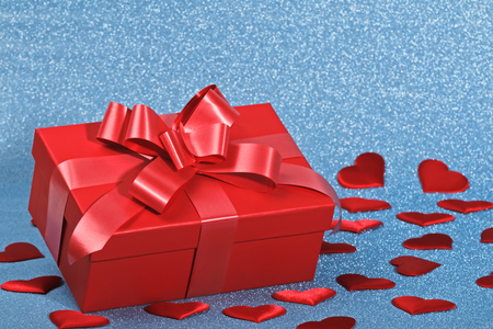 Closeup of a red box with a gift and hearts on a blue shiny background. Valentines day celebration concept. Stock Photo