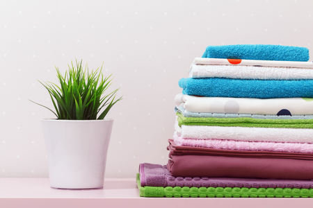 On the dresser there is a stack of clean ironed bed linen, folded multi-colored towels and a home plant stands.