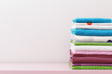 On the dresser there is a stack of clean ironed bed linen and folded colored towels. Stock fotó