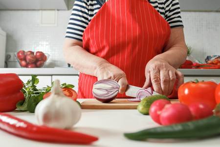 Senior woman cooking at home in the kitchen, cutting onions on a wooden board. Healthy fresh food.