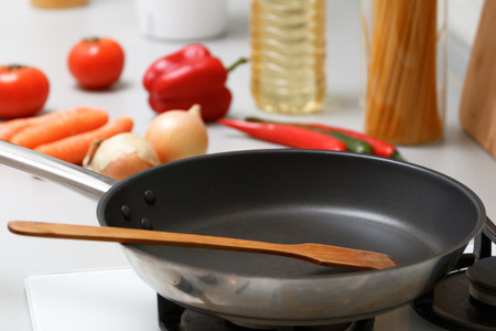 An empty pan with a wooden spatula for stirring stands on a gas stove, next to fresh vegetables and pasta Reklamní fotografie