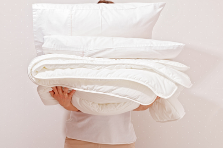 Woman holding a pile of bedding for sleeping. Household Imagens - 116424702