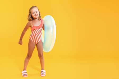 Happy child little girl in a bathing suit with a swimming ring on a colored yellow background. Vacation concept 스톡 콘텐츠
