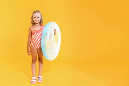 Portrait of a happy child little girl in a bathing suit with a swimming ring on a colored yellow background. Vacation concept