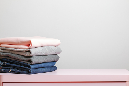 On a pink table is a stack of folded clothes. Gray background. Close-up