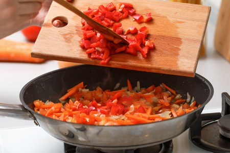 Homemade cooking. A woman with a wooden cutting board adds red pepper to a hot pan with vegetable oil, onion, tomato and carrots. Close-up. 免版税图像