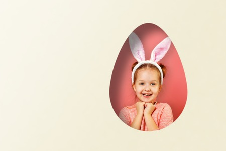 Cute little baby girl with bunny ears. A child in a hole in the shape of an egg on a colored pink and white background. Easter concept.