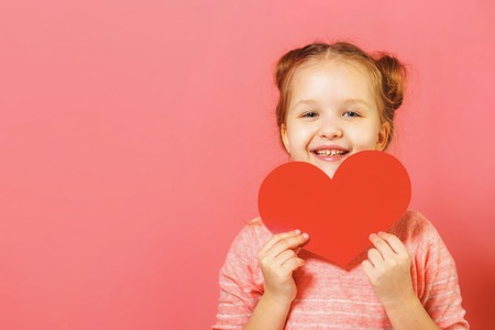 Closeup portrait of a cute little girl with buns of hair on a pink background. Child holding heart
