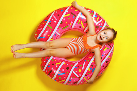 A little child girl in a swimwear suit lying on a donut inflatable circle. Yellow background. Top view.