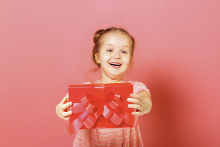 Closeup portrait of a cute little girl with hair buns on pink background. At the child in the hands of the box with a gift.
