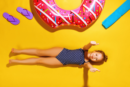 Top view of a little girl lying on the floor with slippers, a towel and an inflatable circle donut on the side. A child in a bathing suit is resting on a yellow background and shows his thumb.