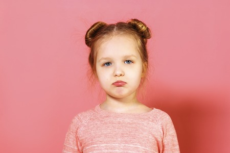 Closeup portrait of upset little girl with wisps of hair over pink background. The child pouted his lips.
