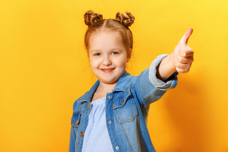Closeup portrait of a cute attractive little child girl showing thumb up on yellow background.