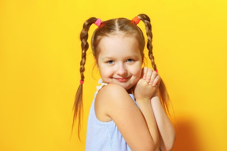 Closeup portrait of charming cute little child girl on yellow background.