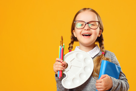 Portrait of a cheerful little child girl on a yellow background. Schoolgirl holds a book, pencils, brushes and a palette. The concept of education.
