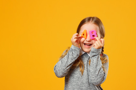 Portrait of a cheerful little girl child on a yellow background. Schoolgirl holds the letters A and B. The concept of education and school. Imagens