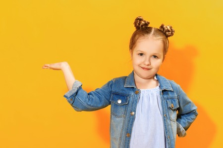 Closeup portrait of a cute attractive little girl on yellow background. The child holds in the palm a copy of the empty blank space and looks into the camera. Foto de archivo