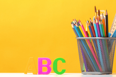 Set of stationery. Pencils, brushes, paints, letters of the alphabet A, B, C on the background of the yellow wall. The concept of education. Back to school. Copy space. Stok Fotoğraf