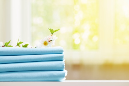 Closeup stack of blue clean bedding on the table. Blurred background. Copy space. 免版税图像 - 124360578