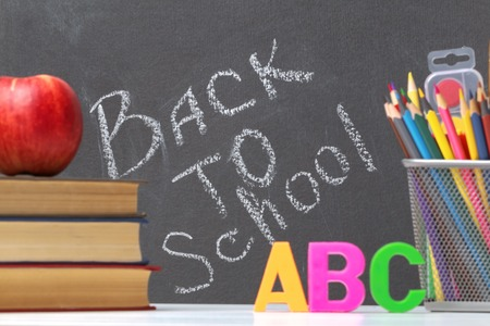 A stack of textbooks, an apple, letters of the alphabet A, B, C, pencils, brushes, paints against a black chalkboard background. The concept of education. Inscription back to school. 免版税图像