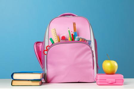 Schüler-Set. Rosa Rucksack mit Schreibwaren, ein Stapel Bücher, eine Lunchbox, ein Apfel auf dem Tisch auf blauem Grund. Zurück zur Schule. Standard-Bild