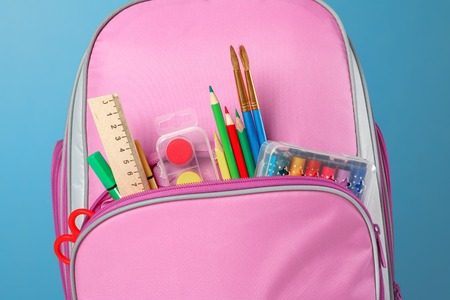 Closeup of pink backpack with office supplies against a blue background. Back to school. The concept of education.