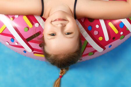 Closeup cute little girl in a bathing suit lying on a donut inflatable circle. Baby upside down. Summer concept. Blue background