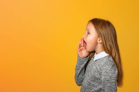 The little girl screams loudly to the side with a hand over her mouth. Close-up. Yellow background. Copy space. Banque d'images