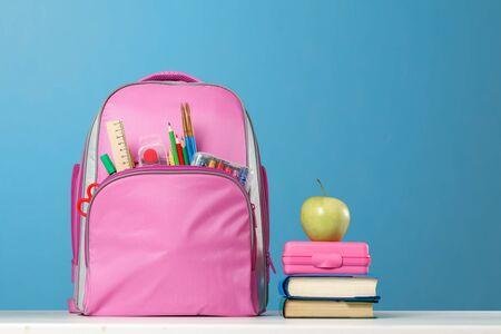 Ensemble étudiant. Sac à dos rose avec papeterie, une pile de livres, une boîte à lunch, une pomme sur la table sur fond bleu. Retour à l'école. Banque d'images