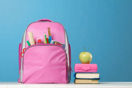 Student set. Pink backpack with stationery, a stack of books, a lunchbox, an apple on the table on a blue background. Back to school.