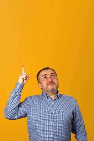 Handsome bearded man in a shirt, points his finger in upwards on a yellow background. Copy space