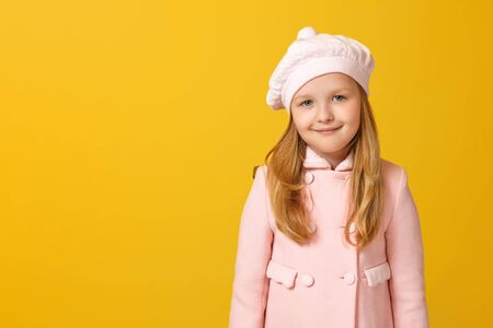 Portrait of a cheerful child in a pink coat and beret on a yellow background. Little girl blonde looks into the camera. Autumn concept. Copy space