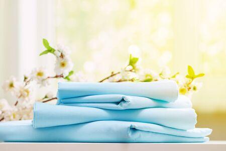 Pila de primer plano de ropa de cama limpia azul en una cómoda. Fondo borroso. Luz solar desde la ventana.