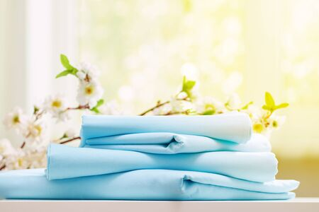 Pila del primo piano di biancheria da letto pulita blu su un comò. Sfondo sfocato. Luce solare dalla finestra.