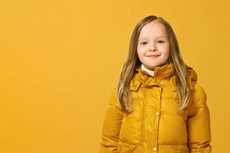 Portrait of a cheerful little girl in jacket over yellow background. Autumn concept. Copy space