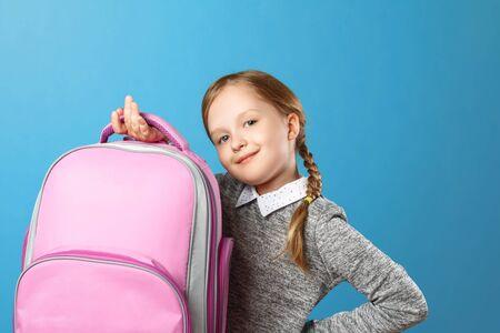 Nahaufnahmeporträt eines Schulmädchens des kleinen Mädchens auf einem blauen Hintergrund. Das Kind hält eine Tasche. Zurück zur Schule. Das Konzept der Bildung. Standard-Bild