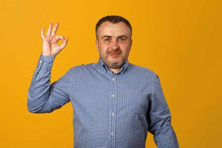 A young man in a shirt shows the ok sign and looks into the camera. Yellow background. Close-up.