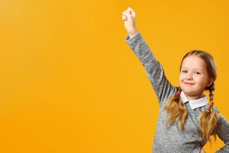 Closeup portrait of a little girl on a yellow background. The child raised his hand up. The concept of success and education. Copy space.