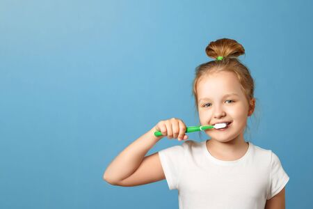 Closeup portrait of a little girl on a blue background. A child brushes his teeth with a toothbrush. The concept of daily hygiene. Copy space