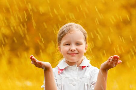 Portrait of a cute charming little girl standing in autumn park in the rain. The child stretched out his hands and collects the drops in his palm. Blurred background.