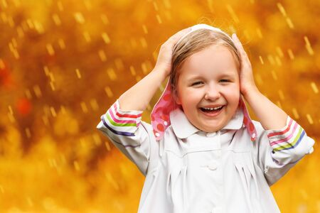 Portrait of a cute charming laughing little girl standing in autumn park in the rain. Blurred background. Standard-Bild
