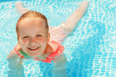 Charming little girl swims in the pool. The child is smiling and looking at the camera.
